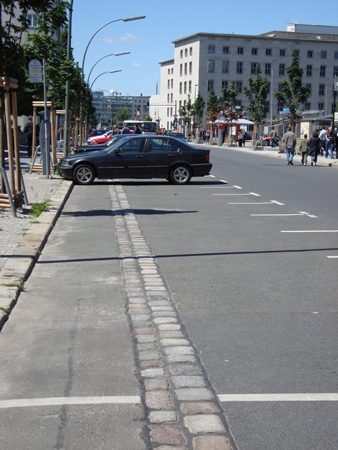 A line of cobbled stones in the road show the path of the Berlin Wall.  East Berlin, West Berlin, East Berlin, West Berlin ....