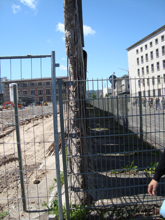 Berlin Wall was not very thick. Rather than razor wires, it was capped off by concrete piping. To the right was East Berlin.